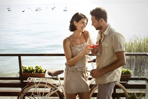 couple drinking in front of bicycle