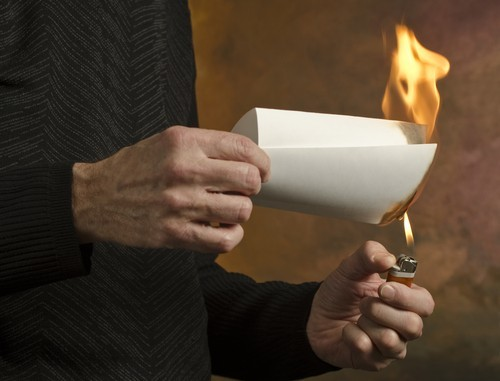 man burning piece of paper
