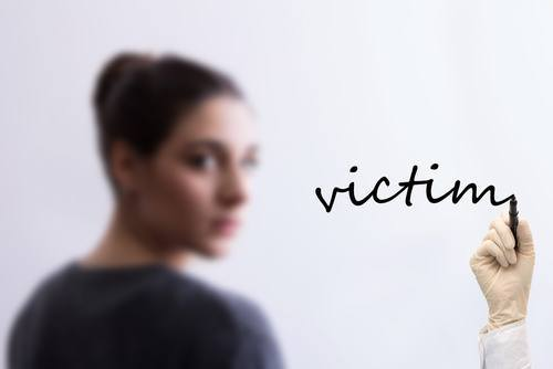 "blurred female in the background with someone writing ""victim"" in foreground"