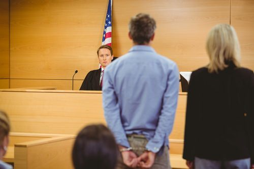 a defendant standing beside attorney in front of judge