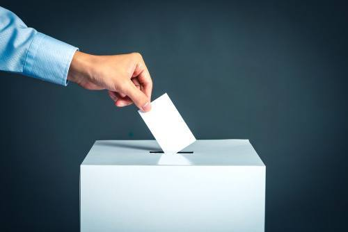 hand shown casting a ballot into ballot box