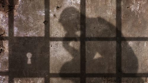 shadow of thinking man in jail cell