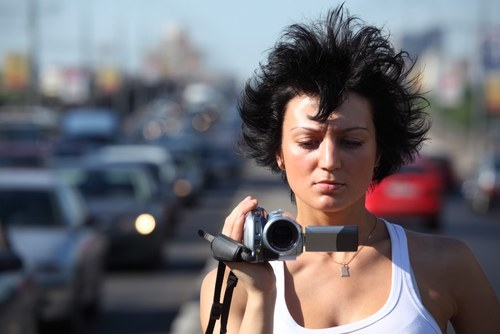 Girl with dark, spiky hair standing on freeway with video camera