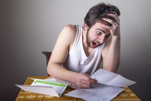 Bearded young man in tank top seated at desk and holding hand to his head in shock as he looks at his auto insurance bill
