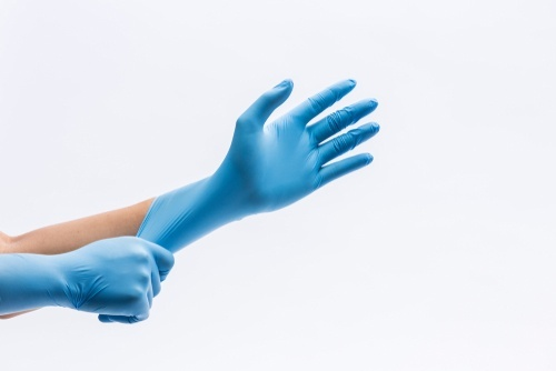 person putting on a latex glove