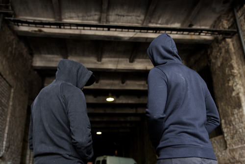 two youths wearing hoodies in a dark place
