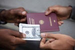 Hands exchanging cash for a fake passport