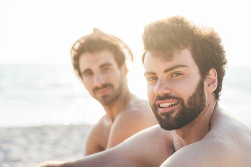 two men smiling on the beach
