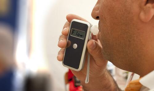 man blowing breathalyzer