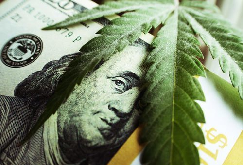 marijuana leaf on top of a 100 dollar bill