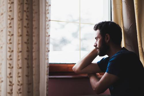 young man depressed by window