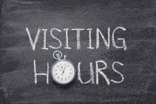 "chalk writing on the ground that says ""visiting hours"""