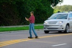 A man jaywalking with a car approaching.