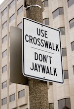 A traffic sign ordering pedestrians to use the crosswalks.