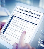 "Tablet computer showing document with ""criminal records"" text"