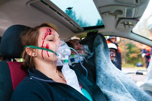 Girl with bloody face and oxygen mask inside emergency vehicle
