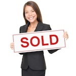 "Woman holding ""Sold"" sign"