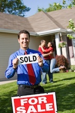 "Man holding ""Sold"" sign in front of a ""for sale"" house with a happy couple in the background."