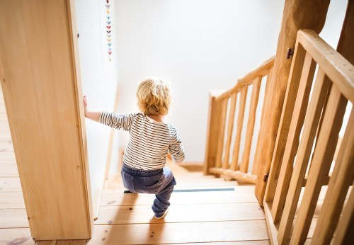 young child attempting to walk down stairs unassisted