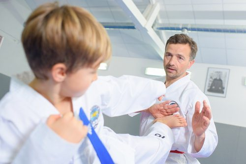 Adult male practicing martial art with young boy