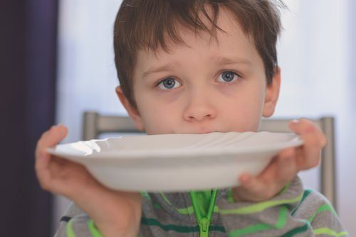hungry boy holding an empty plate