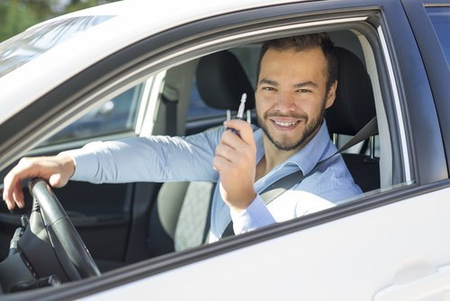man smiling with keys to a car in his hand