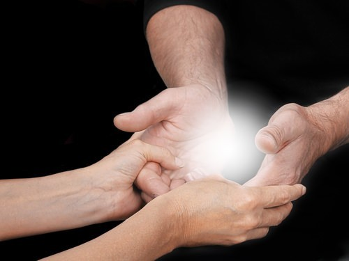 two hands sharing a cloud of energy or spirit