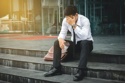 man in suit sitting on a step looking stressed