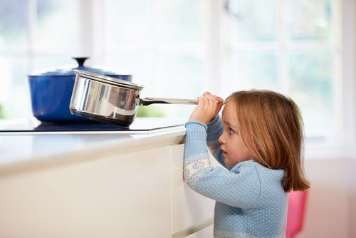 young girl tilting kitchen pot towards herself