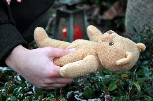 teddy bear being placed on a grave