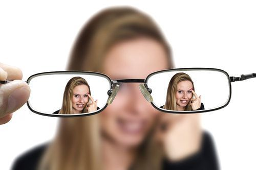 eyeglasses held at distance focusing on female model