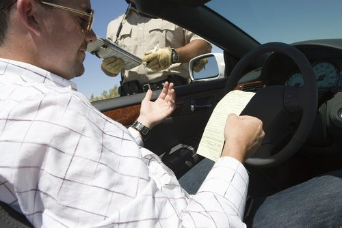 officer handing driver a traffic ticket