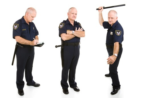 a policeman writing up a ticket, looking menacing, and holding a baton