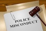 """Paper that says """"police misconduct"""" with gavel to the side"""