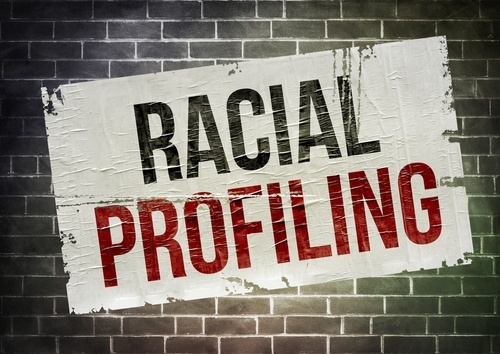 "Sign that says ""racial profiling"" on a brick wall"