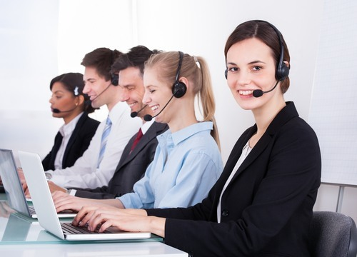 Team of five receptionists with headsets and laptops