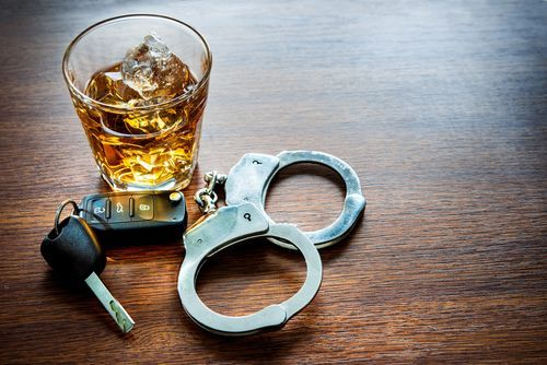 car key, drink, and handcuffs - DUI can be a felony in Colorado if it is the 4th offense or is there is an accident where a another person is injured or killed.