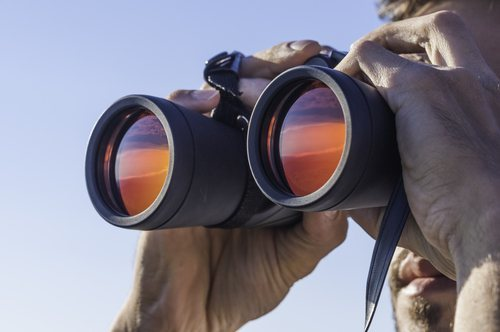 man looking through binoculars. california invasion of privacy legal defense