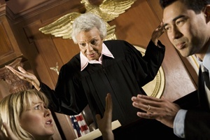 Judge in black robes yelling at lawyer and his female client in a courtroom