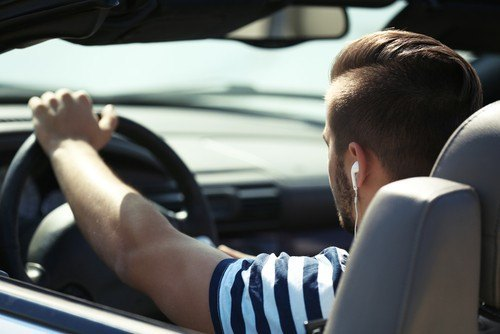 man wearing headphones while driving - illegal in california - attorneys