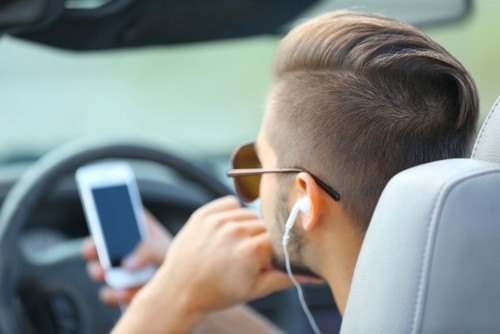 Man texting and driving as an example of acting with negligence per se.