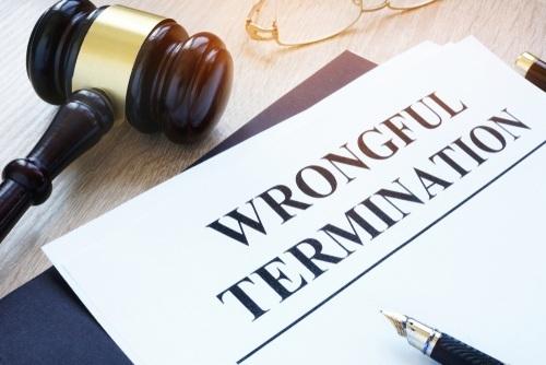 """wrongful termination"" written on paper near gavel"