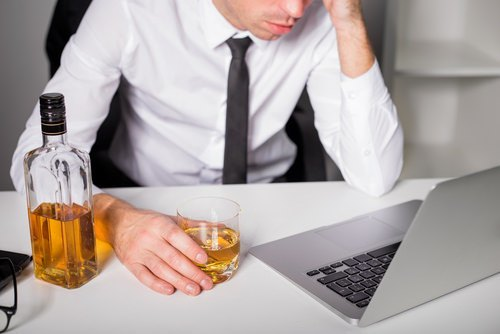 man at computer drinking (filing a work injury lawsuit in Nevada)