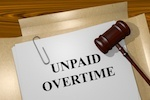 "paper that says ""unpaid overtime' and gavel"
