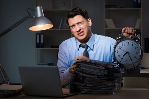 Overworked man behind a desk holding a clock