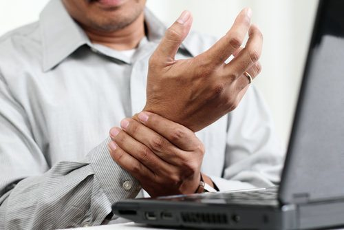 man at computer with injured hand (bringing a job injury lawsuit in Nevada)
