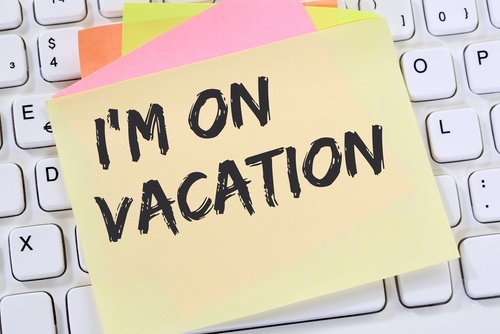 "post-it that says ""I'm on vacation"" stuck on a keyboard"