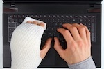 hand with cast over keyboard