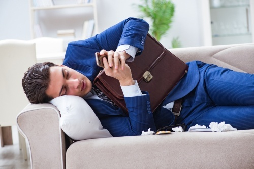man in suit with briefcase on couch sick