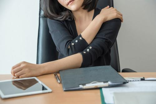 female worker at her desk clutching her shoulder in pain